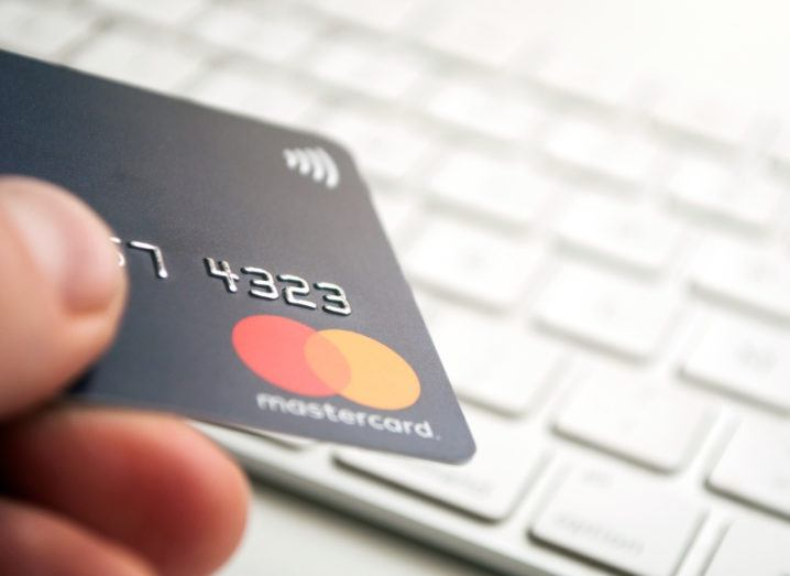 A close-up of a hand holding a Mastercard credit card in front of a white computer keyboard.