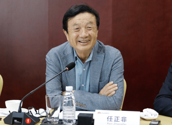 Huawei founder and CEO Ren Zhengfei smiles at a media briefing table with a microphone.