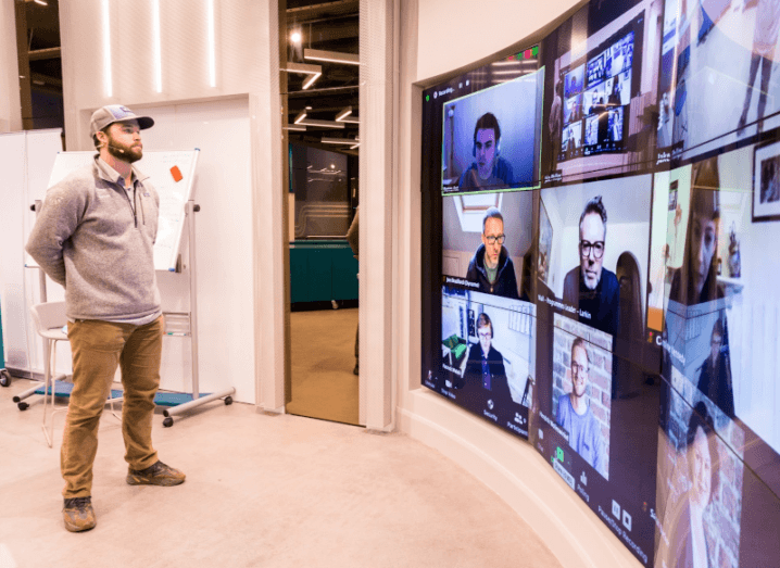 A man stands in Dogpatch Labs in Dublin, while speaking to a number of people on a large screen.