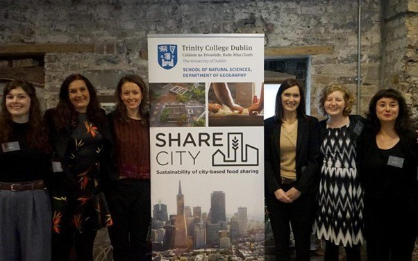 Six women stand either side of a large sign that says ShareCity.