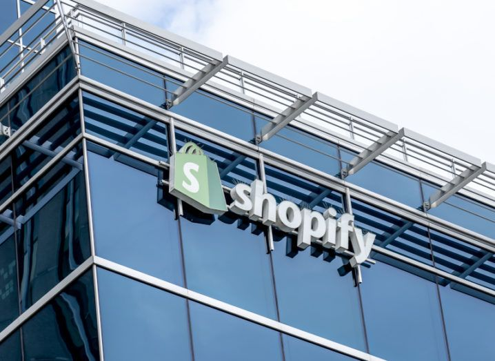 The Shopify logo at the top of a large glass office building.