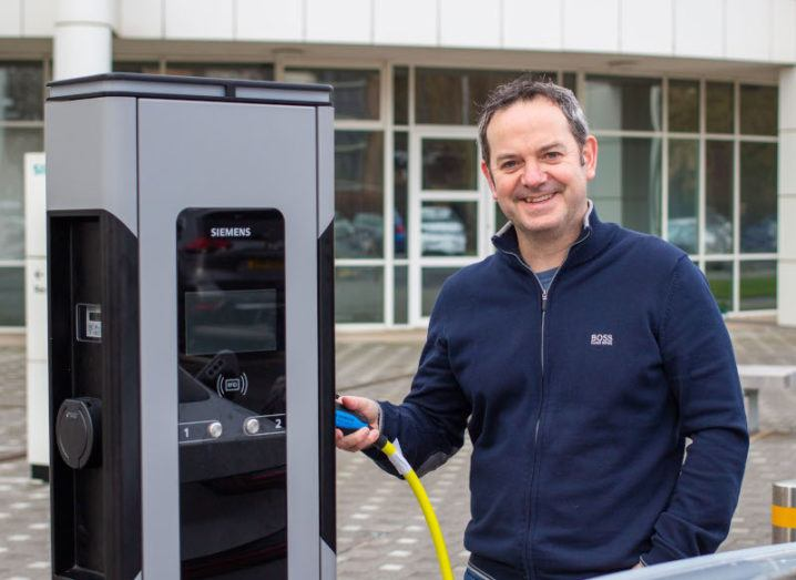 Bernard Magee stands beside a Siemens charging station for EVs, holding the plug in place.