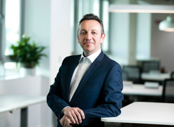 Steve Coakley of BT Ireland leans against a white surface while smiling at the camera. He is dressed in a business suit.