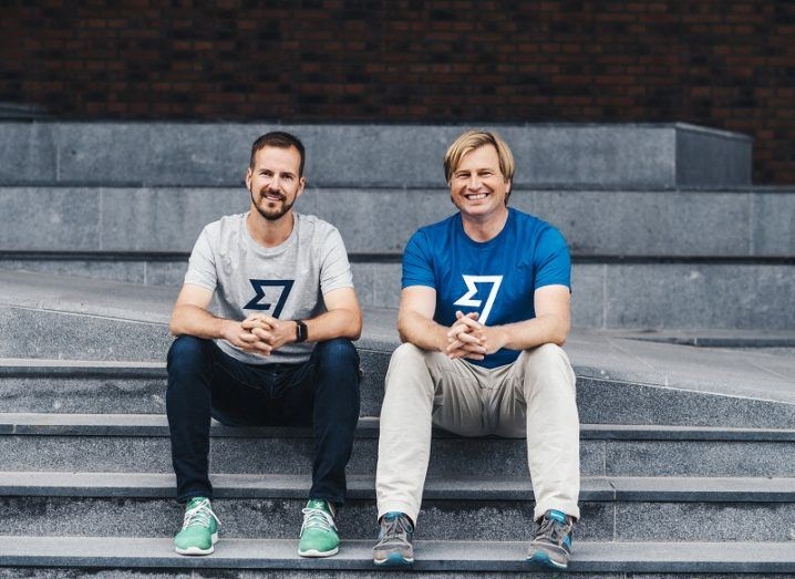 The two founders of TransferWise are sitting on a step, wearing T-shirts that feature the company's logo.