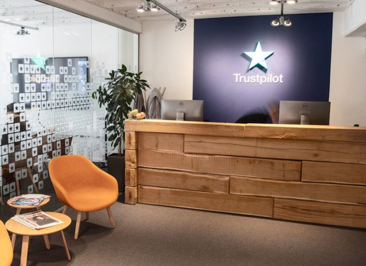 A cosy reception area in an office with a Trustpilot logo on the back wall behind the reception desk.