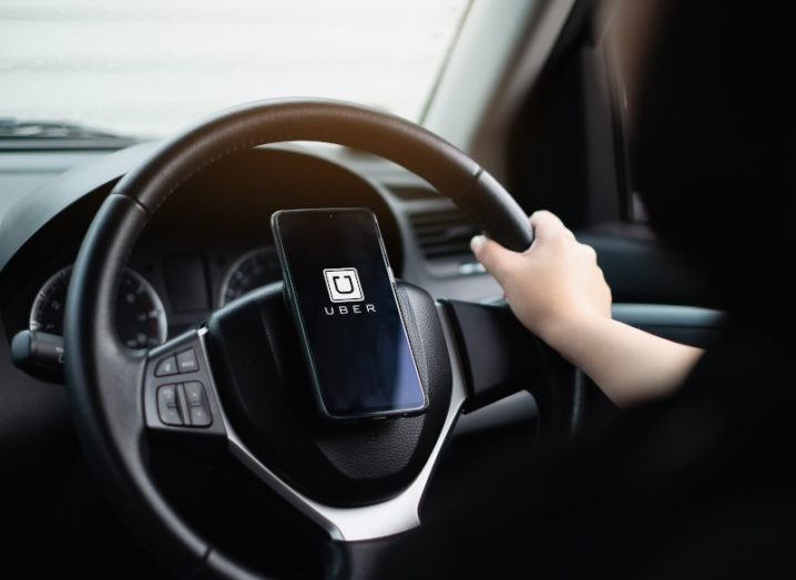 The inside of a car, looking at the steering wheel from behind. There is one hand on the wheel and a phone attached to the centre with an Uber logo on the screen.
