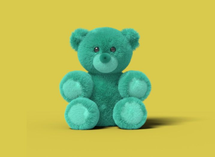 A blue teddy bear sits against a mustard-yellow background.