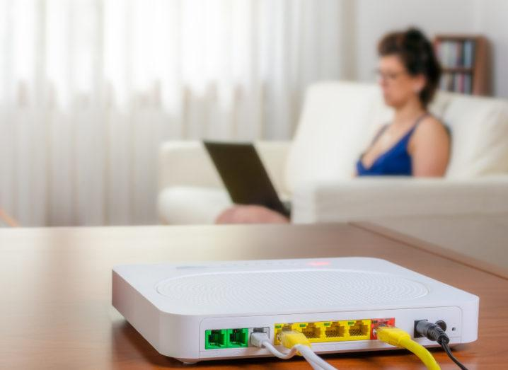 A white broadband modem router on a table in a living room. A woman using a laptop while sitting on the sofa is in background.