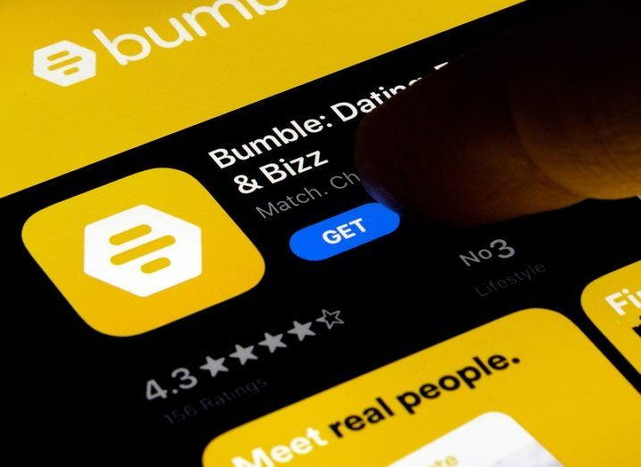 Close-up of a smartphone screen showing a finger hovering over the button to download the Bumble app.