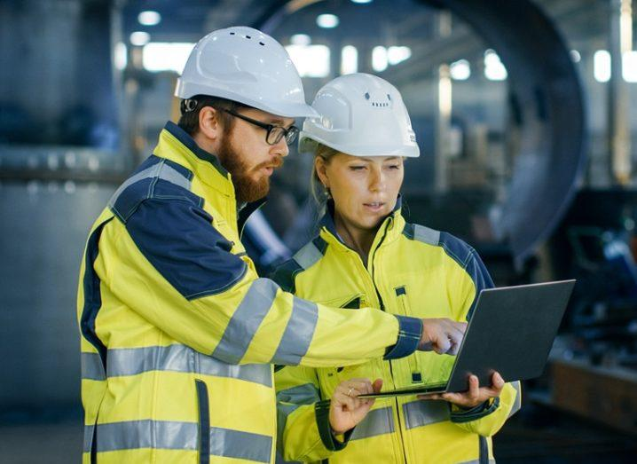 Two engineers in protective clothing stand on-site looking at a laptop.
