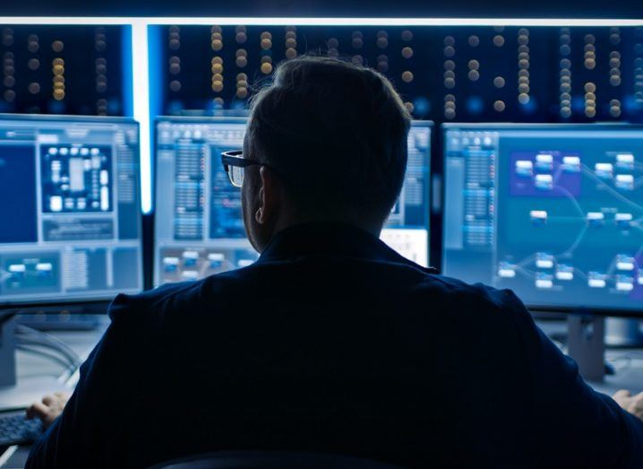Silhouette of a man working a multiple computer screens.