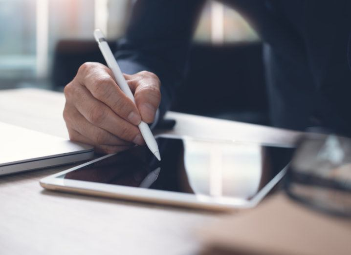 A businessperson signing a tablet with a stylus pen, symbolising an e-signature.