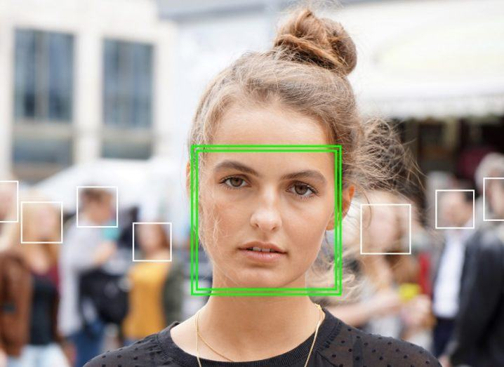 Image of a woman with a green square over her face, as if she has been picked out by facial recognition software.