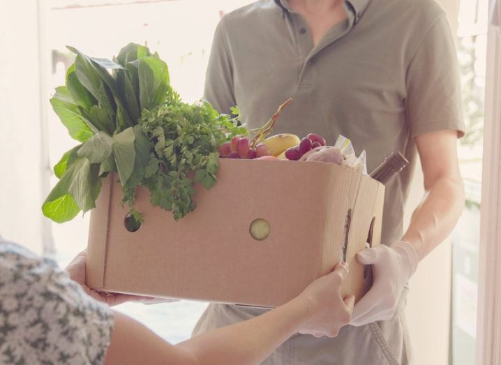 A man in a brown polo shirt is handing a cardboard box filled with fruit and vegetables to a woman.