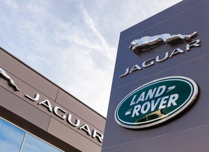 A Jaguar Land Rover sign outside a Jaguar building against a blue sky.