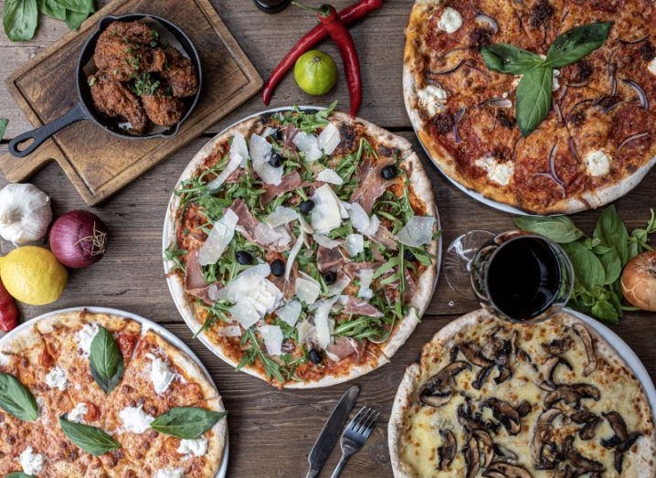 A bird's-eye shot of a wooden table full of pizzas and other food that you might order from Just Eat Takeaway.