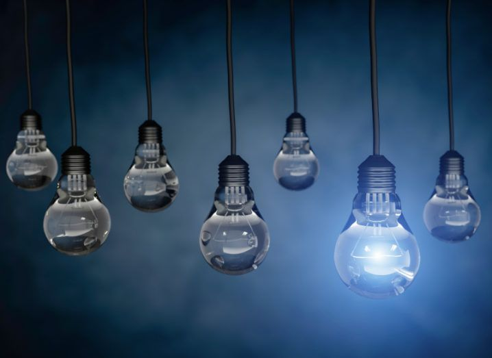 Seven lightbulbs hanging against a dark blue background. One of the bulbs is on with a bright blue light.