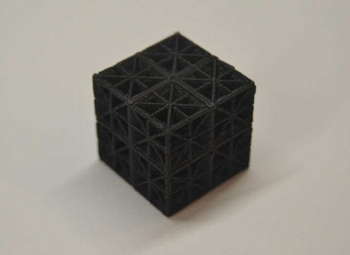 A black 3D-printed material in the shape of a cube with a lattice design on all sides.