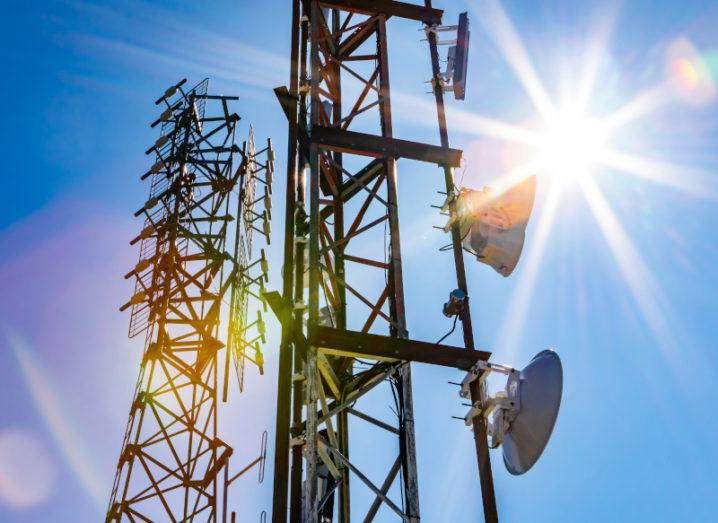 A bright sun shines over two mobile mast towers against a blue sky.