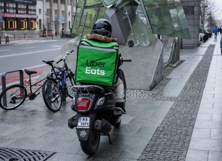The back of delivery driver on a motorcycle on a city street with an Uber Eats green bag on the back.