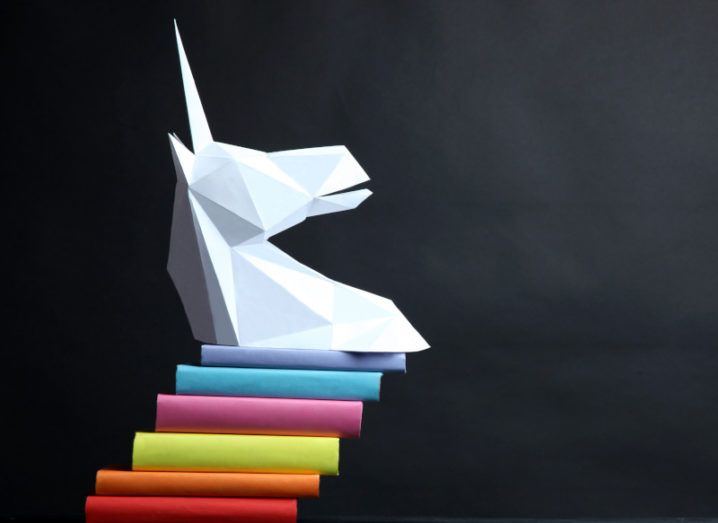 A white unicorn head statue balances on a colourful stack of blocks against a charcoal background.