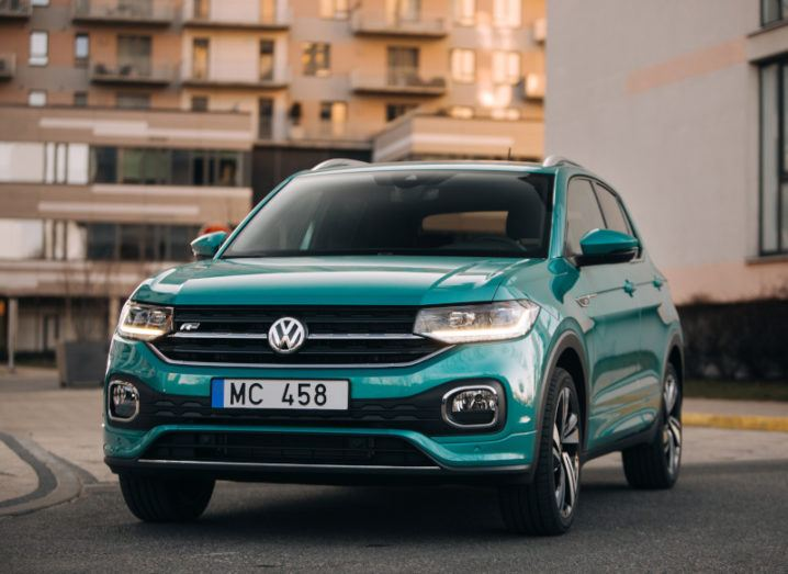 A green-blue Volkswagen T-Cross on a road with no one in the car.