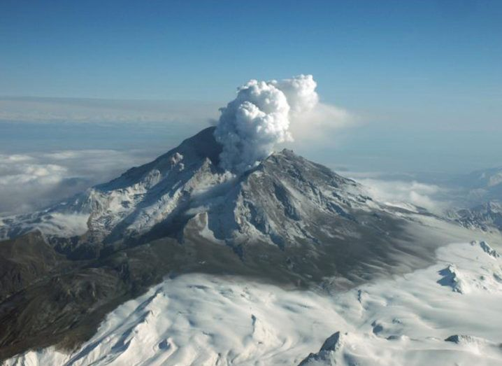 Aerial view of Mount Redoubt, Alaska, from a distance. Steam is rising from the volcano following the 2009 eruption.