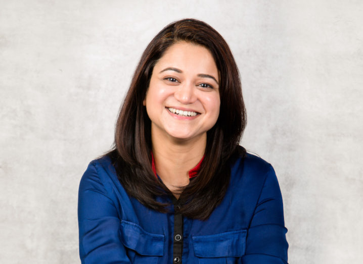 A headshot of Bhawna Singh, CTO of Glassdoor. She's wearing a blue shirt and smiling at the camera.