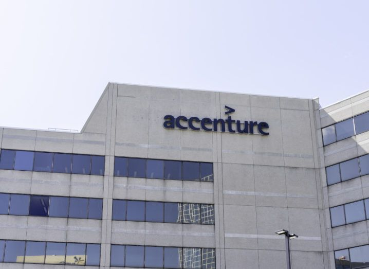 A large stone office building against a clear blue sky with the Accenture logo on the top of the building.