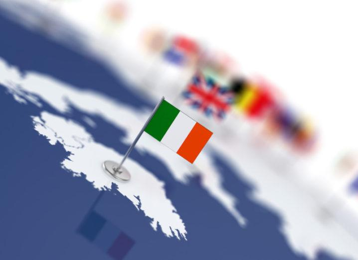 A miniature Irish flag is placed on the country's outline on a world map. Other flags placed on the map are just seen in the background.
