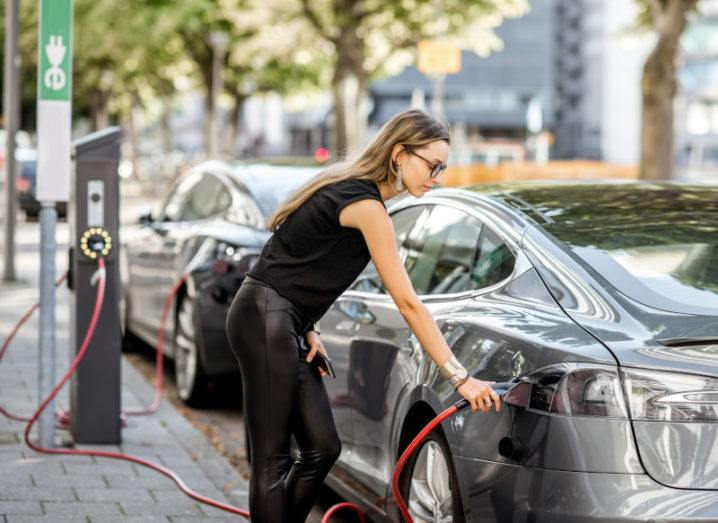A woman is plugging a connector into her electric vehicle on a city street.
