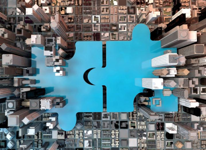 Illustration of two blue jigsaw pieces connecting amid a city business district of tall buildings seen from the sky.