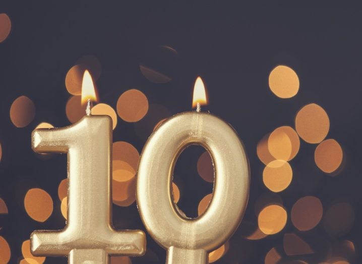 Candles shaped like the number 10 are lit against a bokeh background.