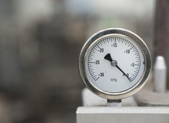 A silver pressure gauge or barometer.