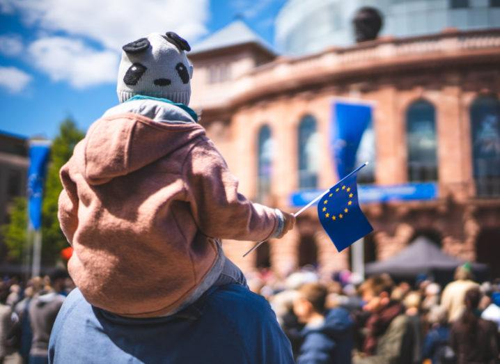 A child is held up on his father's shoulders amid a crowd. He holds a small EU flag in his hand.