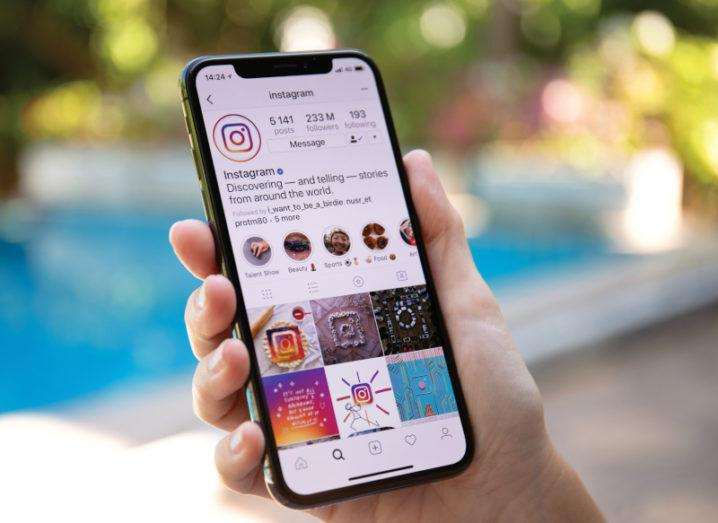 A hand holds a smartphone accessing the Instagram account on the Instagram app. The display shows a grid of images underneath the brand's bio and Stories.