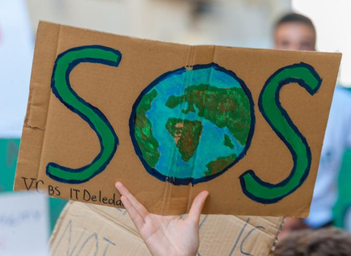 A demonstrator is holding up a home-made sign on a piece of cardboard that says 'SOS', but the letter O is an image of the Earth.
