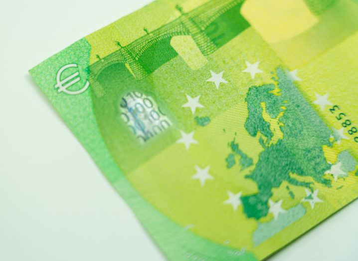 Close-up on the reverse of a €100 bank note, showing a map of Europe in green.