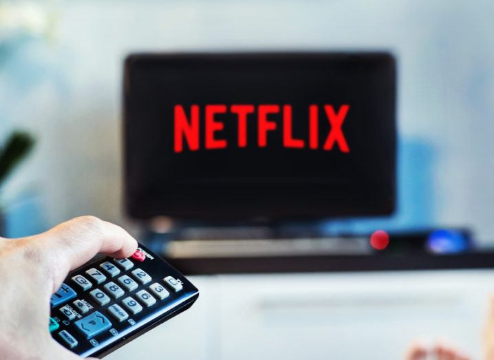 A man is pointing a remote control at a TV that has the Netflix logo open on it.