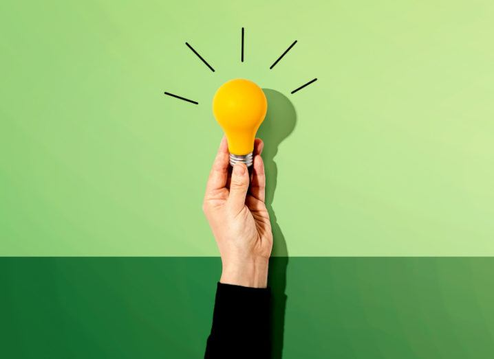 A person's hand is holding a yellow lightbulb up against a bright green background.