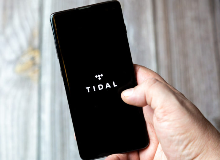 A hand holding a smartphone displaying the Tidal logo on a black background.