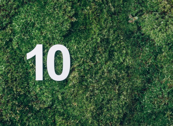 A white paper cut-out of the number 10 laying in a patch of rich green grass.