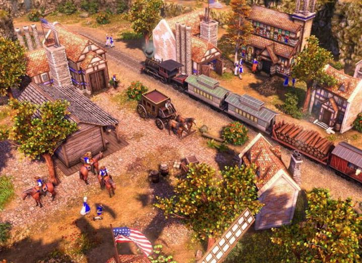 A screenshot of the Age of Empires video game, showing a group of houses with characters on horses as a train drives through the middle.