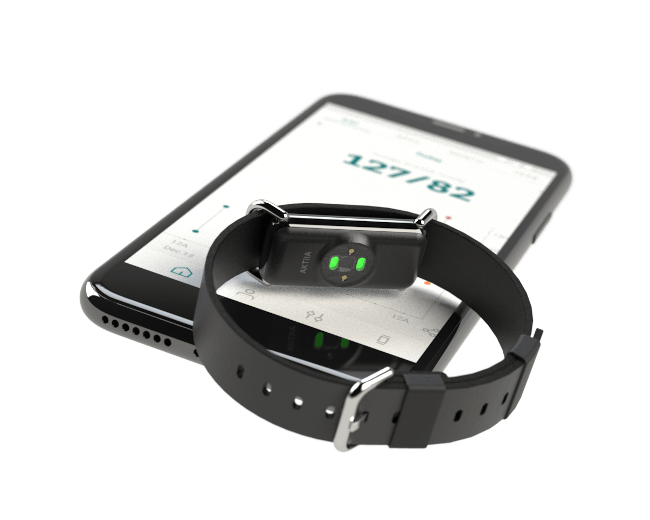 A bracelet device with optical sensors on the reverse face sits on top of a smartphone showing the Aktiia blood pressure monitoring app.