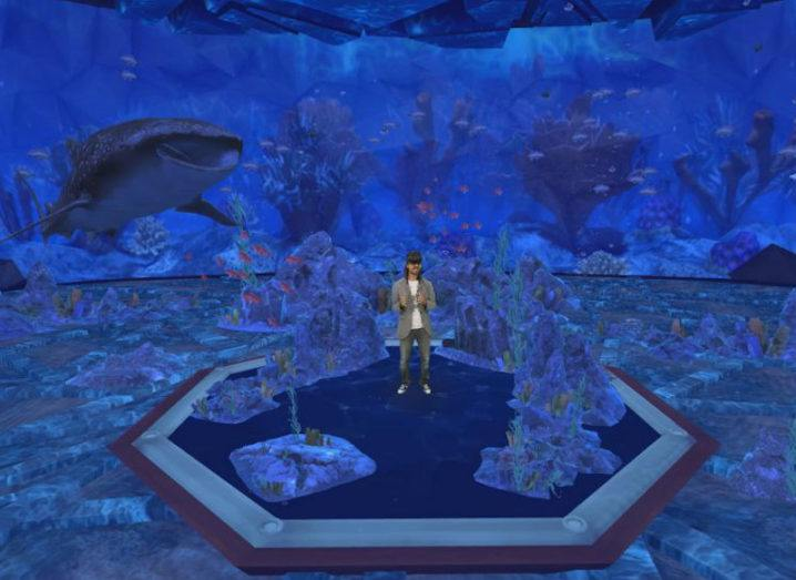 Microsoft's Alex Kipman stands on a virtual stage wearing a VR headset, in a space that looks like he is underwater.