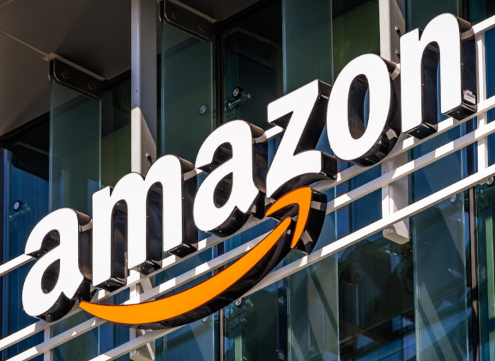 A large Amazon logo on a large glass building.