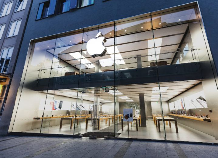 A white Apple logo on a large office with a largely glass front.