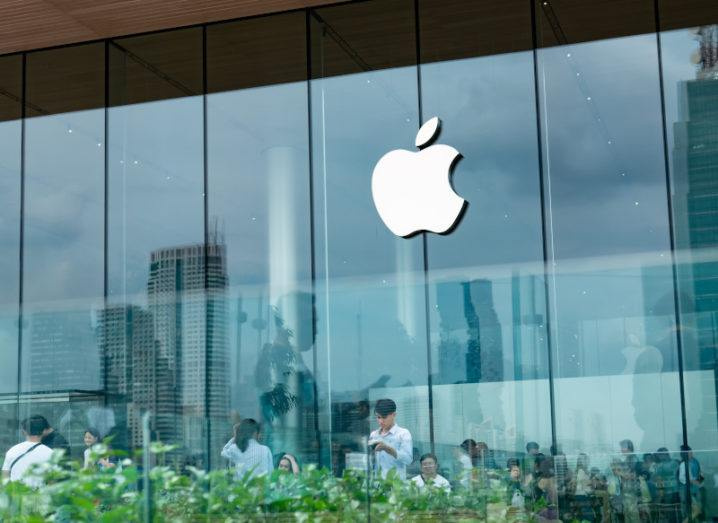 A white Apple logo on a glass building with several workers inside. The glass reflection shows some greenery along the bottom.