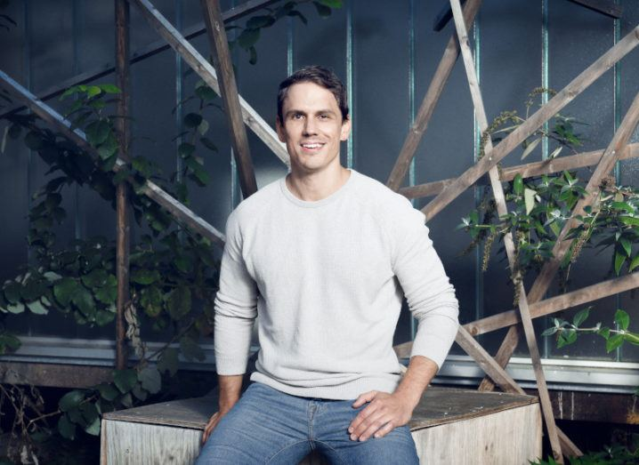A man in jeans and a light grey sweater sits casually on a wooden platform, surrounded by green foliage.