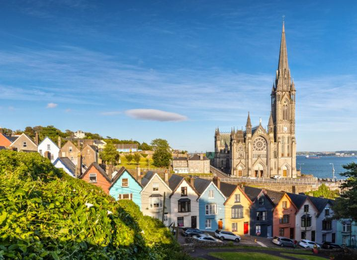 A large cathedral in Cobh near Cork in Ireland. It stands behind a row of colourful houses against a blue sky.